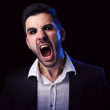 Scary man with black eyes and fangs. Scary man in suit with black eyes and fangs screaming against black background royalty free stock photos