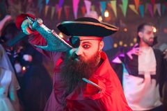 Scary man dressed up like a party holding an axe at halloween celebration. Scary men dressed up like a party holding an axe at halloween celebration. Woman royalty free stock image