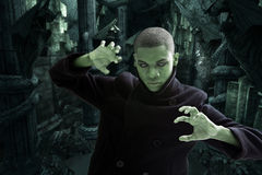 Scary man in dungeon. Green man with smokey white eyes, strong expression and black coat in dungeon hall way, isolated Stock Image