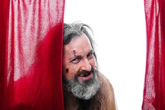 Scary man. Scary looking man between a red curtain Stock Photography