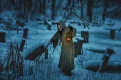 Scary man with scythe is the winter snow. Stock Photography