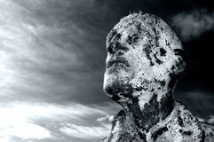 Scary Mans Face. A statue of the scary face of a man against a stormy sky royalty free stock images