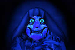 Scary mask in black clothes on a blue background Stock Photography