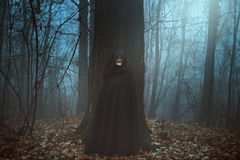 Scary masked man in a misty forest royalty free stock photography