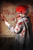 Scary medical clown injecting horror into limb Royalty Free Stock Image