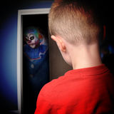 Scary Monster Clown in Boys Closet. A scary clown is coming out of a boys closet in his bedroom at night for a nightmare or scary concept