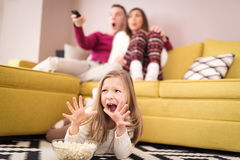 Scary Movie. Beautiful young family watching a scary movie at living room. Selective focus Royalty Free Stock Photos
