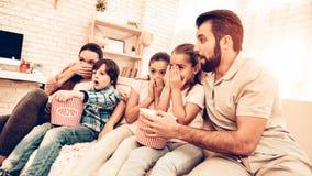 Scary Movie de observação da família alegre em casa foto de stock