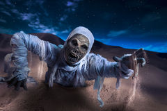 Scary mummy in a desert at night. Scary Halloween mummy in desert with dramatic lighting stock photography