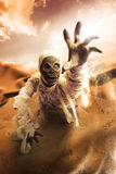 Scary mummy in a desert at sunset. Scary Halloween mummy in hot desert with dramatic lighting stock image