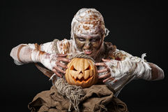 Scary mummy holding the pumpkin Royalty Free Stock Photo