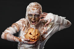 Scary mummy waves her arms with pumpkin Royalty Free Stock Photography