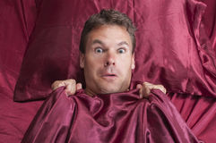 Scary nightmare. Caucasian man pulls covers up to neck as he trembles in fear from nightmare while lying on bed with red sheets Stock Image