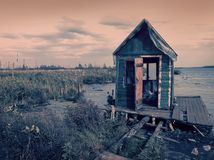 Scary old terrible abandoned hut, wooden creepy house on mysterious empty uninhabited swamp with dead trees and. Monochrome natural background of mistical royalty free stock photos