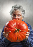 Scary old woman eating a big ripe pumpkin. Halloween theme. Stock Photo