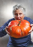 Scary old woman eating a big ripe pumpkin. Halloween theme. Royalty Free Stock Photography