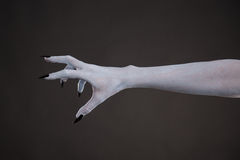 Scary pale skin hand with black nails. Body art for Halloween Stock Photos