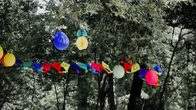 Scary party. Scary slow coloured festoons on pale trees stock video