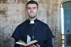 Scary priest with fangs raising eyebrow.  royalty free stock photo