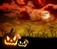 Scary Pumpkin Cloud Background. A scary moon cloud Halloween background with two black pumpkins in the foreground glowing. There are trees and a glow to the sky Royalty Free Stock Photo