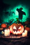 Scary pumpkin on dark field with scarecrows for Halloween. On dark background Royalty Free Stock Image