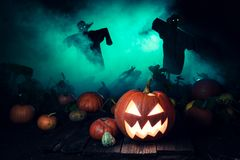 Scary pumpkin with green mist and scarecrows for Halloween. On dark background stock photography