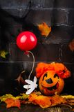 Scary red hair clown made from pumpkin, holding red balloon. Spooky dark Halloween background. Greeting card, space for text Stock Photo