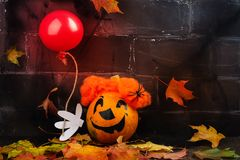 Scary red hair clown made from pumpkin, holding red balloon. Spooky dark Halloween background. Greeting card, space for text Stock Photos