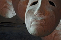 Scary and sad white masks. On the table in the dark royalty free stock photography