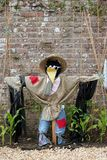 Scary Scarecrow. Scarecrow in a garden next to small sweetcorn plants and bamboo canes, acting as a deterrent to birds. Old brick wall to the rear Royalty Free Stock Images