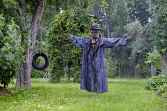 Scary scarecrow in a hat. In garden in cloudy weather. Halloween concept stock photography
