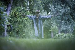 Scary scarecrow in a hat. In garden in cloudy weather. Halloween concept royalty free stock image