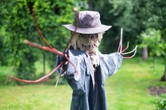 Scary scarecrow in a hat. In garden in cloudy weather. Halloween concept royalty free stock photography