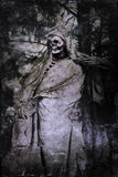 Scary sculpture of a grim reaper. Standing on a cemetery. The picture is processed with a texture and a vignette to reinforce the scary mood Royalty Free Stock Photos