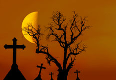 Scary silhouette dead tree and spooky silhouette crosses in mystic graveyard with half moon Royalty Free Stock Image