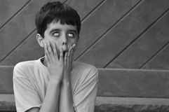 Scary, Silly Face. Young boy makes a scary, silly face to frighten friends. Terrifying actor in black and white Royalty Free Stock Images
