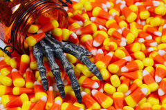 Scary skeleton hand coming out jar into a pile of candy corn. Closeup image of a scary hand coming out of jar into pile of candy corn Royalty Free Stock Photos