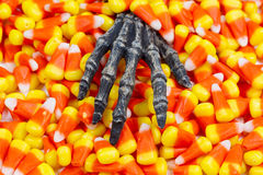 Scary skeleton hand coming out of pile of candy corn Stock Image