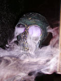 Scary skull. Metal model of a skull steaming violet gas Royalty Free Stock Photography