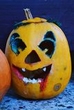 Scary smiling carved halloween jack o lantern with blood like painting on jaw and traces of blight around the eyes. Evening sunlight Royalty Free Stock Images