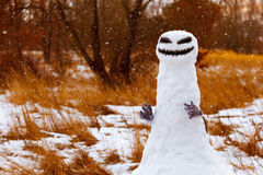 Scary snowman as a monster on a background of yellow grass. Halloween. Royalty Free Stock Photo