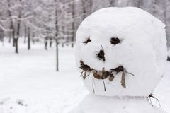 Scary snowman from a horror movie. Sculpture of snow. Strange and terrifying snowman. Playing outdoors in winter. Family winter fun in the forest. Smile and nose stock photo