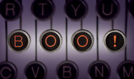 Scary Stories. Image of old typewriter keyboard with scratched chrome keys that spell out BOO! in orange letters. Lighting and focus are centered on BOO Stock Image