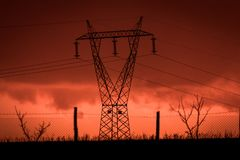 Scary sunset, with red sky and clouds, after storm. Power pylons and industrial fences in devastated landscape. B Evil environment royalty free stock photography