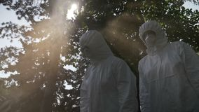 Scary team of biohazard engineers workers team dressed in hazmat suit protecting against leaking toxic gas smoke - stock footage