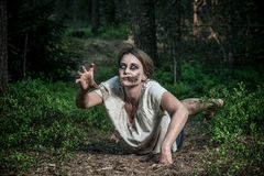 A scary undead zombie girl. Lying on the ground Royalty Free Stock Photography