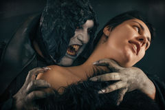 Scary vampire devil biting young woman. Medieval gothic nightmar. E horror. Studio shoot Royalty Free Stock Photo