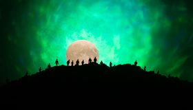 Scary view crowd of zombies on hill with spooky cloudy sky with fog and rising full moon. Silhouette group of zombie walking under. Full moon. Halloween concept Stock Image