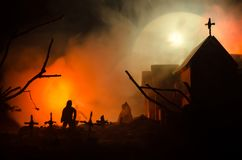 Scary view of zombies at cemetery dead tree, moon, church and spooky cloudy sky with fog, Horror Halloween concept Royalty Free Stock Image