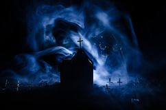 Scary view of zombies at cemetery dead tree, moon, church and spooky cloudy sky with fog, Horror Halloween concept. Toned Royalty Free Stock Image
